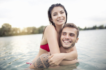 Attractive young couple hugging in lake