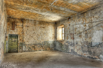 Empty, derelict room in an abandoned prison.