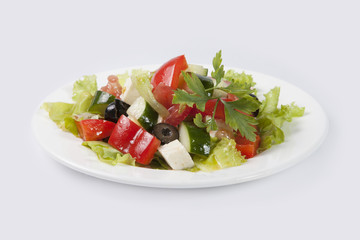 Greek Salad on white plate and gray background