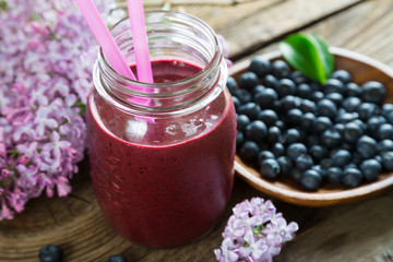 Blueberry smoothie and lilac flowers