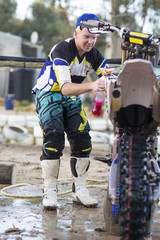 Young male motocross competitor cleaning motorcycle