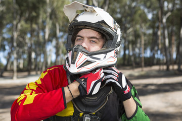 Motocross motorcycle competitor fastening helmet in forest