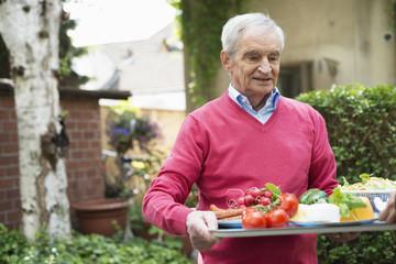 Senior man carrying tray of fresh food