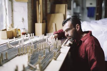Mature craftsman checking organ pipes in pipe organ workshop