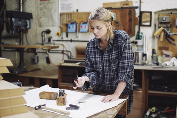 Young craftswoman checking components on workbench in pipe organ workshop