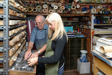 Senior man and young woman selecting book letterpress in traditional bookbinding workshop