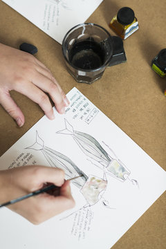 Young womans hands painting fashion design on work table