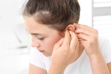Dziewczynka zakłada aparat słuchowy.