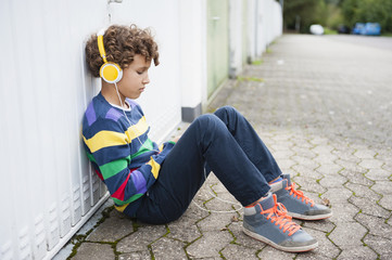 Sullen boy sitting leaning against wall listening to headphones