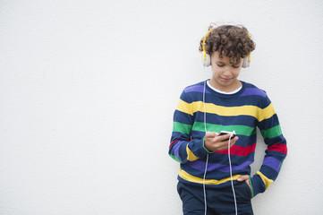 Boy leaning against wall choosing music on smartphone