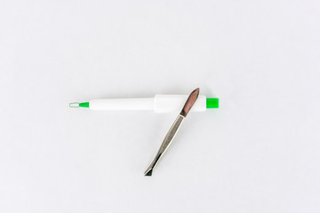 Tick remover and steel tweezers on white background, studio shot.