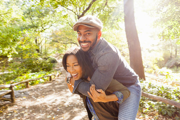 Couple playing piggy back, Central Park, New York, USA