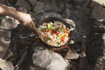 Hand of teenage boy cooking stir fry on campfire, Indiahoma, Oklahoma, USA