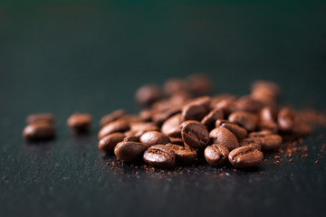 Coffee beans on a wooden old green background, closeup with free space for text, horizontal, selective focus