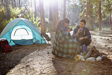 Young camping couple drinking coffee in forest, Los Angeles, California, USA