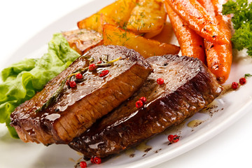 Grilled beef steaks and vegetables