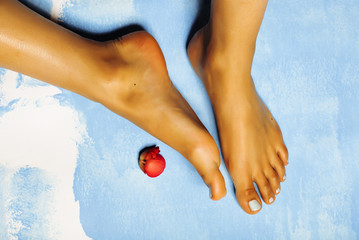 stylish african Female perfect shape feet, blue pedicure with pink flower, vacation on sea concept