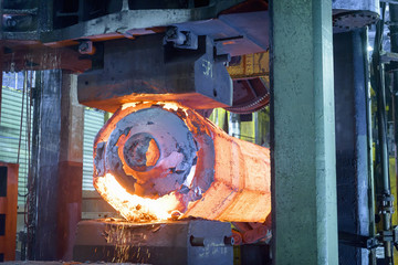 Hot steel in forging press in steelworks