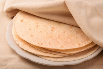 Stack of tortilla covered with neat cloth