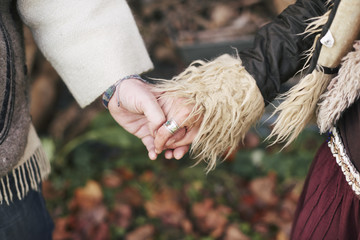 Close up of mature hippy couple holding hands