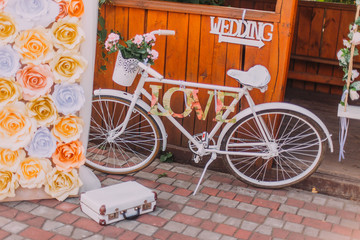 Decorative white bicycle with basket of flowers and word love, indoors