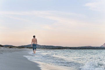 Rear view of mid adult man strolling on beach, Sardinia, Italy