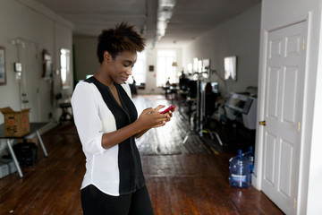 Woman using smartphone, home office