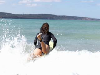 Rear view of female surfer in sea