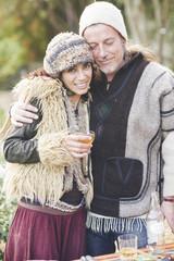 Portrait of mature hippy couple drinking cider in garden