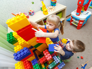 Very serious little boy and girl build big block tower
