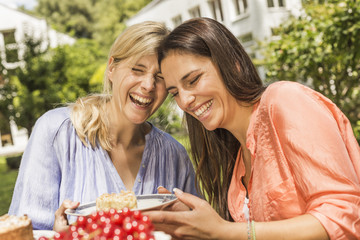 Two female friends in garden, laughing, holding plate with dessert