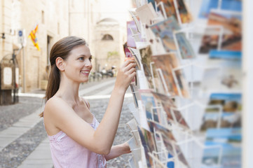 Mid adult woman choosing postcard from rack, Sardinia, Italy