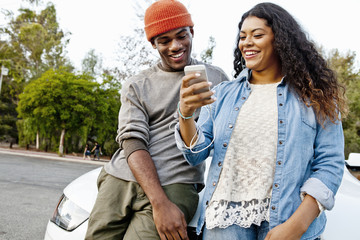 Young couple in car park reading smartphone texts