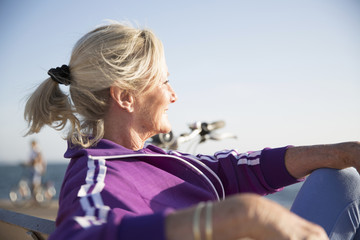 Senior woman enjoying ocean view on bench