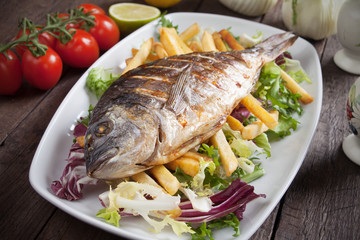 Grilled fish with french fries and salad