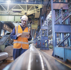 Engineer checking steel part with digital tablet in engineering factory