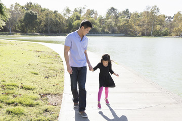 Mature man and daughter holding hands in park