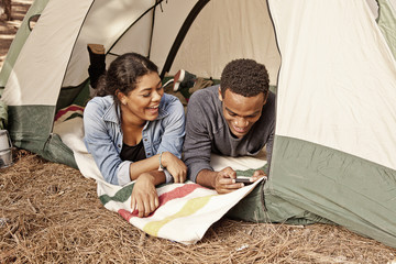 Young couple lying in tent and reading texts on smartphone