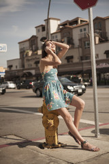 Young woman sitting on fire hydrant, using mobile phone, laughing