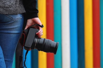 photographer holding  camera, close-up. Back view, Selective focus. colored vertical stripes in the background.