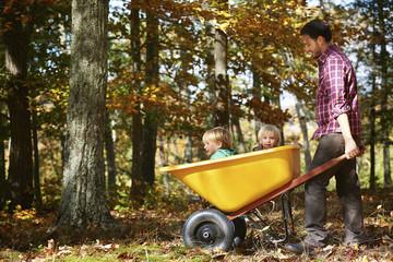 Father pushing children in wheelbarrow