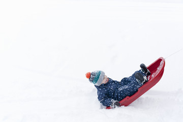 Boy playing on his toboggan in the snow