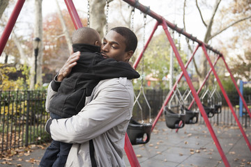 Father and toddler son hugging in park
