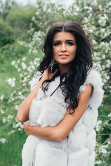 A beautiful dark-skinned woman in a white dress in the lush apple orchard