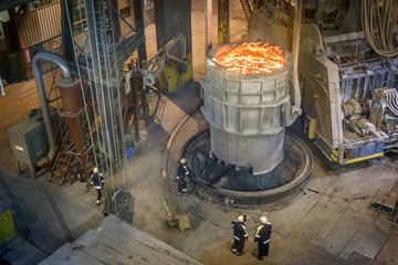 High angle view of steel workers inspecting molten steel in flask