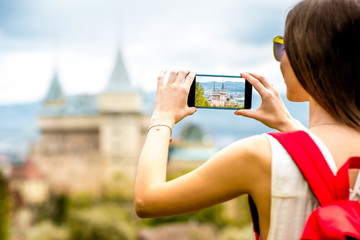 Young female traveler photographing with smart phone Bojnice castle in Slovakia