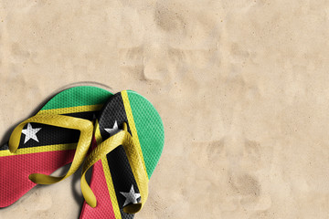 Thongs with flag of Saint Kitts and Nevis, on beach sand
