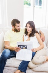 Couple reading newspaper in living room