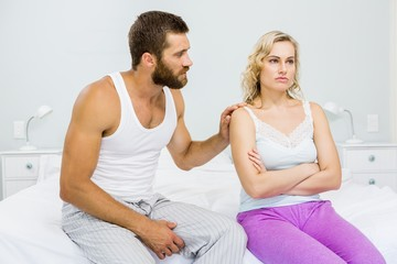 Young couple arguing on bed