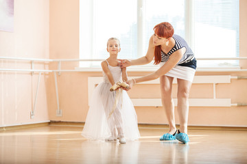 Ballet teacher adjusting arm position of young ballerina dancing with pointe shoes